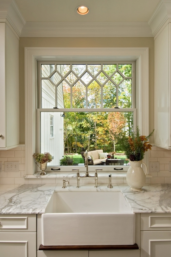 white bathroom windowsill featuring a potted cacti and bonsai trees