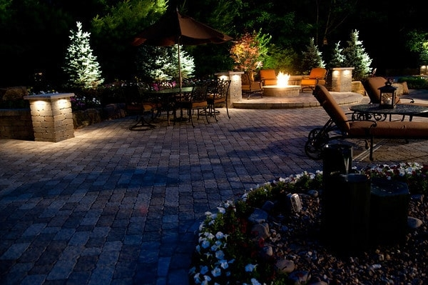 features a fire pit, walls and a dining area by  BAC McCune Outdoor Living