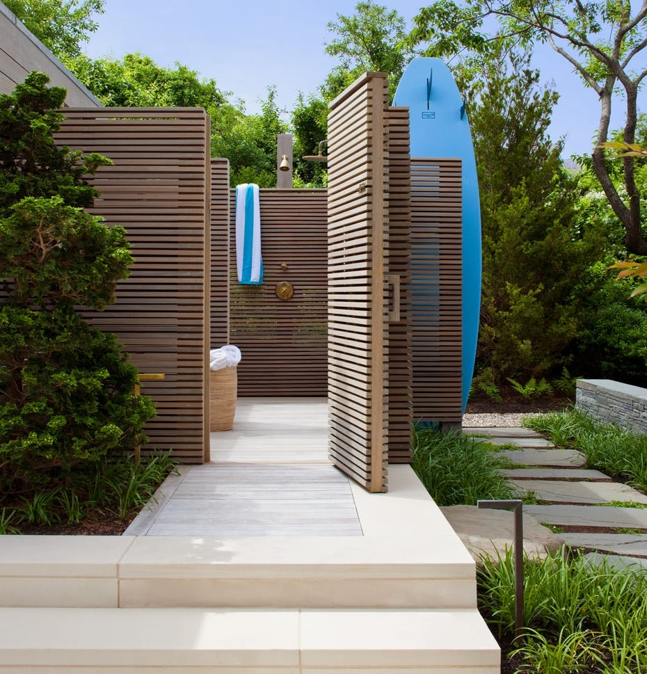 An outdoor bathroom featuring an open shower area with a private courtyard